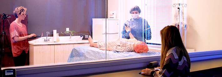 Woman looking through two-way mirror while surgeon simulates use during human factors usability study.