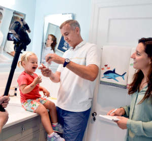 Design researcher observing father giving his daughter oral medication.
