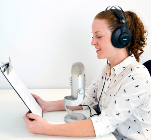 Woman creating voiceover wearing headphones and looking at script.