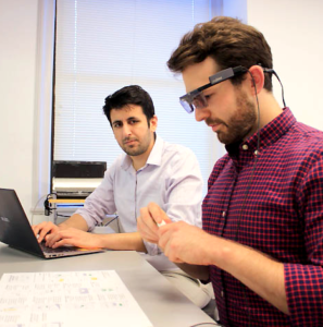 Researcher conducting usability study with man wearing eye tracking glasses.